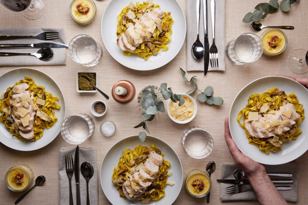 Table with four bowls of pasta topped with grilled chicken and parmesan, with a lemon posset dessert